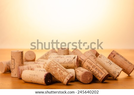 "Several Corks on wood. "" Mis en Bouteille"" (""filled in the bottle or bottled"") or the Origin of the Wine and or the Vintage is printed on them. Background is kept in warm light to represent the sun. - stock photo"