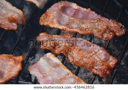 Several crispy smoked grilled barbecue bacon slices, cooked on bbq smoke grill, close up