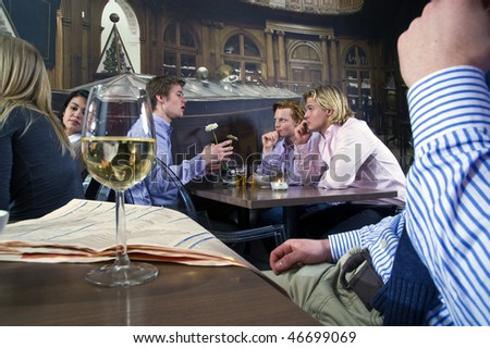 several customers having a discussion in a bar - stock photo
