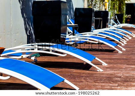 Several deckchairs near the swimming pool - stock photo