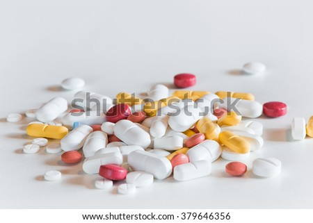 several different colored and sized medicine drug pills on white
