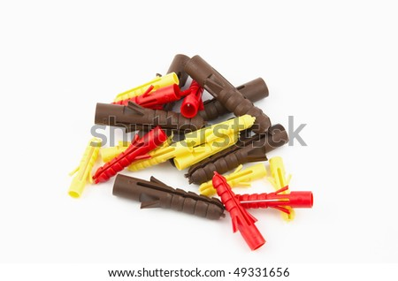 Several different sized brown, yellow and red wall plugs for holding screws in walls - stock photo