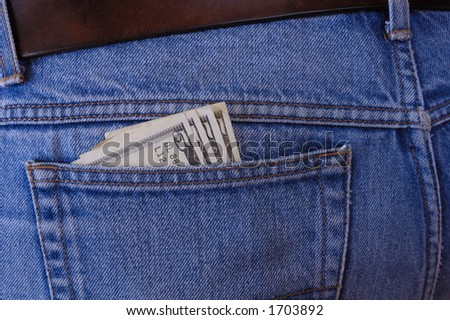 Several 5 dollar bills poke out of the rear pocket of someone's jeans. A temptation for a pickpocket. - stock photo