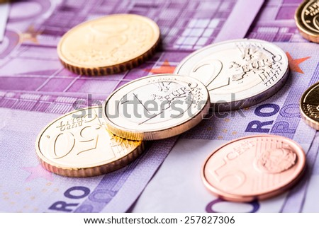 Several 500 euro banknotes and coins are adjacent. Symbolic photo for wealt. - stock photo