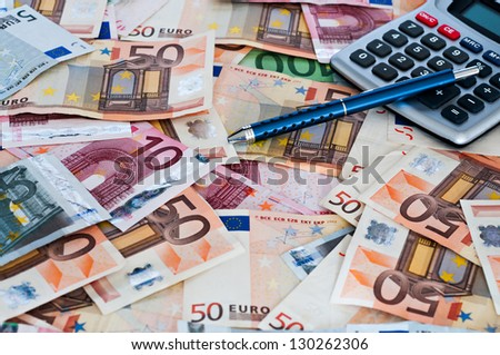 Several Euro notes with calculator and pen - stock photo