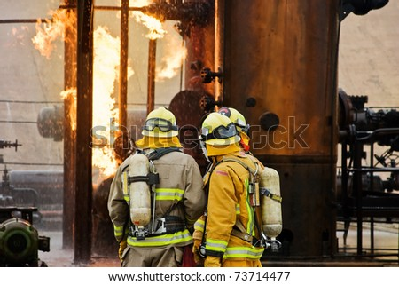 Several firefighters go over the plan of attack. - stock photo
