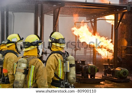 Several firefighters wait for the plan of attack. - stock photo