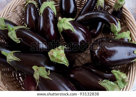Several fresh eggplants arranged in basket - stock photo