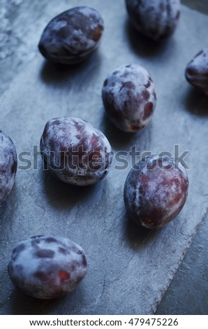 Several fresh plums on a dark stone plate