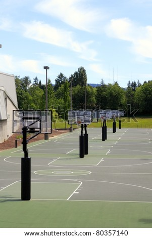 Several green basketball courts outdoors with a landscape and sunny sky with some clouds on the first day of summer. - stock photo