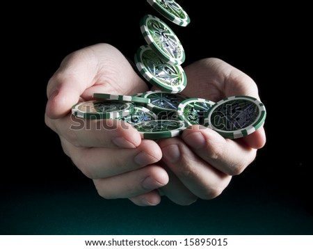 Several green twenty five valued chips falling on a pair of hands isolated over a black background. - stock photo