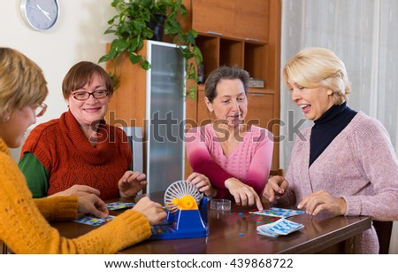 Several happy female pensioners playing board game at the room in the home