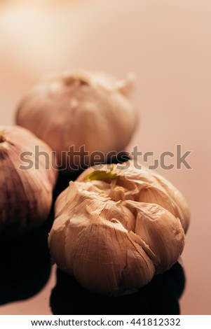 several heads of garlic on a dark mirror background.
