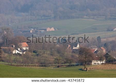 Several houses on a hillside in green fields.  Limburg, Netherlands - stock photo