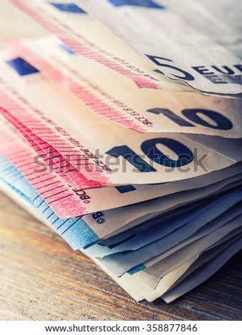 Several hundred euro banknotes stacked by value. Euro money concept. Euro banknotes. Euro currency. Banknotes stacked on each other in different positions. Toned photo. - stock photo