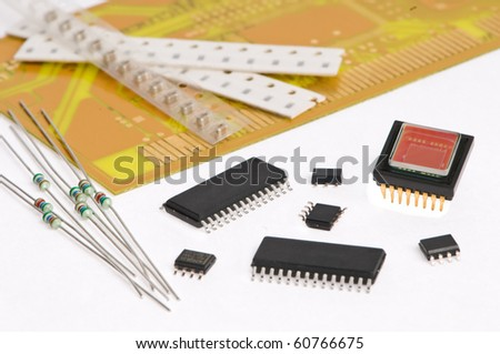 several integrated microelectronics components and yellow microcircuit board - stock photo
