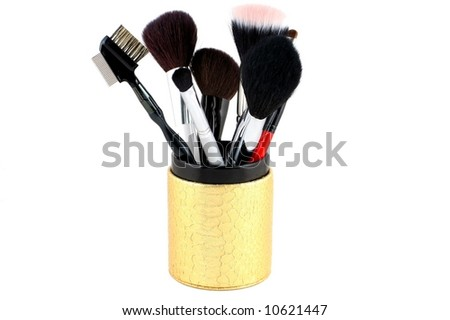 several large makeup brushes in a container