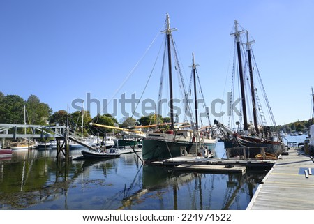 several large sailboats docked by a wooden pier in the Camden Harbor in Maine - stock photo