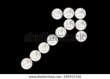 Several metal Russian ruble coins on black background form up arrow - stock photo