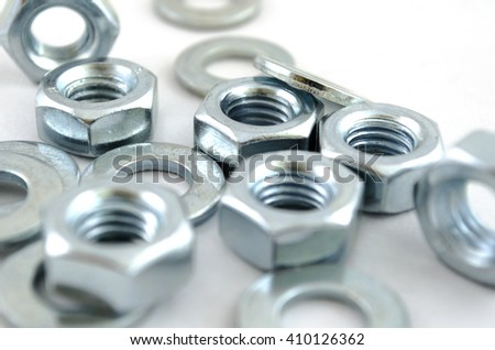 Several metal screw washers and nuts isolated on white background. - stock photo