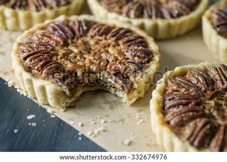 Several mini pecan pies on craft paper and one with a bite missing.