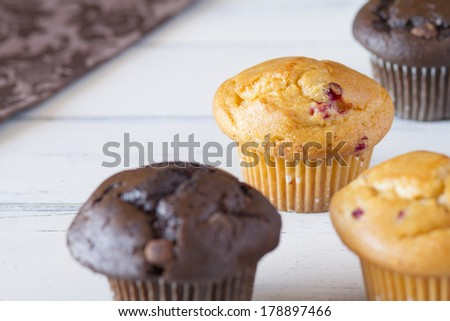 Several muffins and a brown napkin on a white wooden table