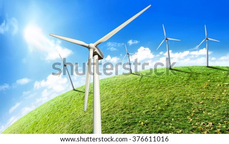 Several of modern wind turbines on a wind farm. Wind turbines on green meadow with blue clear sky. - stock photo