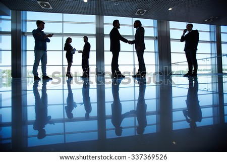 Several office workers standing by the window - stock photo