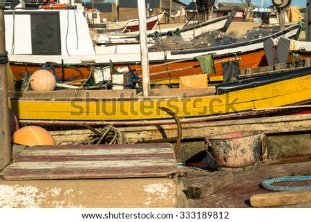 Several old colorful fishing boats resting ashore
