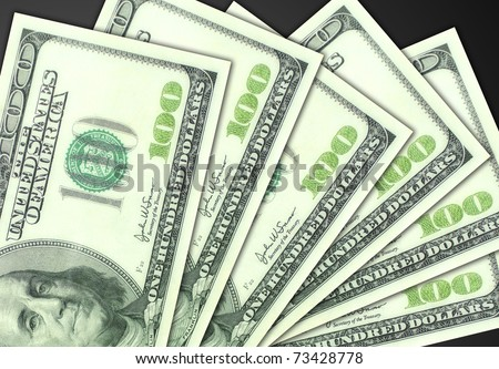 Several one hundred dollar bills fanned out on a plain dark gray background - stock photo