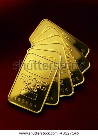Several one ounce gold ingots shot on rich velvet background - stock photo