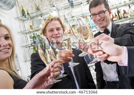 several people toasting with champagne while looking in the camera - stock photo