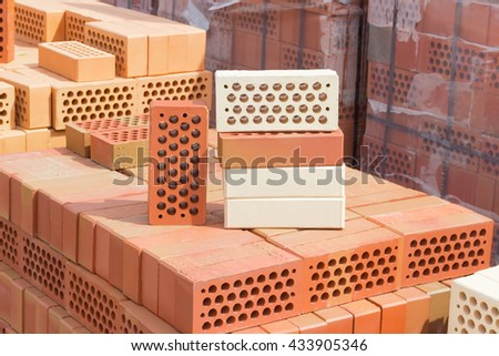 Several Perforated Red And Yellow Bricks With Round Holes On The Pallet Same