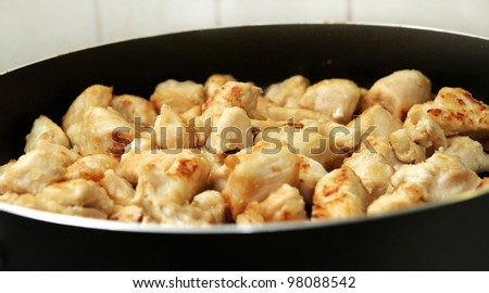 several pieces of chopped up chicken breast browned in a frying pan - stock photo