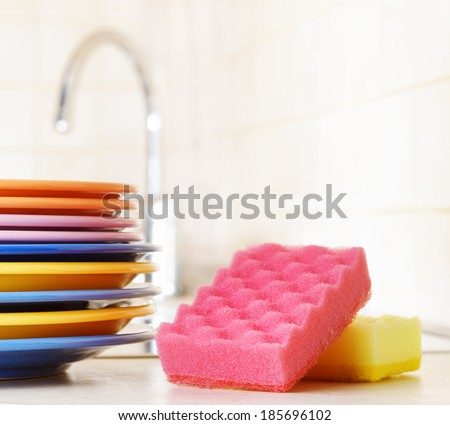 Several plates and a kitchen sponge. Dishwashing concept. - stock photo