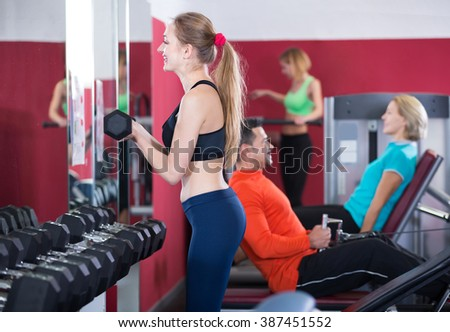 Several positive women and man having training on machines in gym