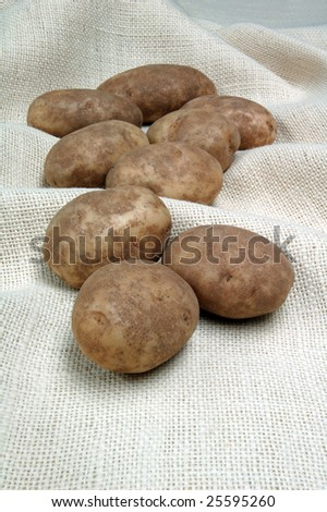 Several potatoes on burlap vertical background