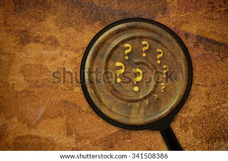 Several question marks written in a spiral under a magnifier - stock photo
