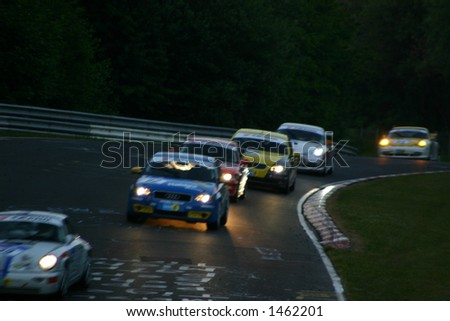 Several race cars in a curve at night - stock photo