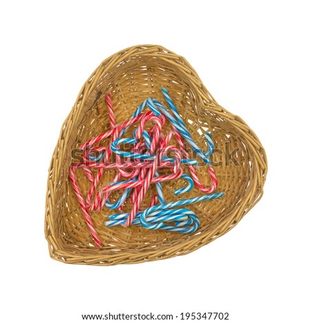 Several red and blue striped candy canes in a wicker heart shaped basket.