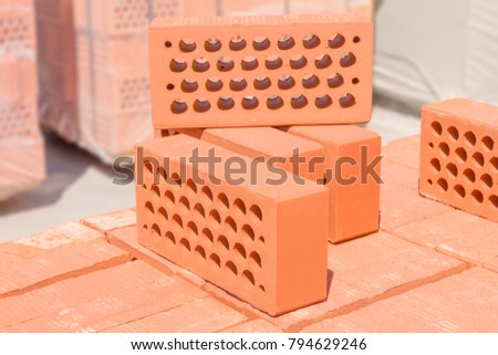 Several Red Perforated Bricks With Round Holes Put On The Pallet Of Same Brick