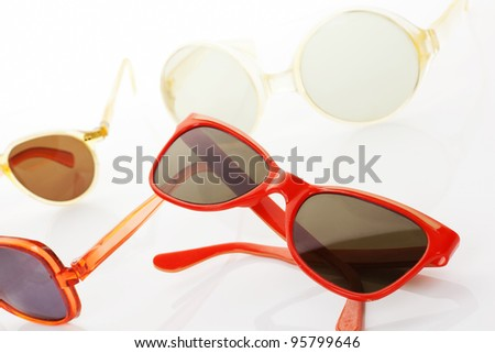 Several retro sunglasses with red, orange, yellow and golden frame isolated on white background. Original vintage objects. - stock photo