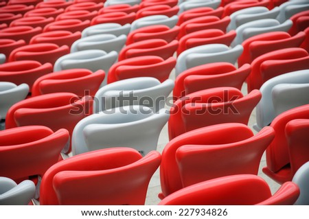 Several rows of red and white stadium seats - stock photo