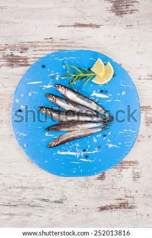 Several sardines on blue round kitchen board, on white wooden background, top view. Mediterranean seafood eating. - stock photo