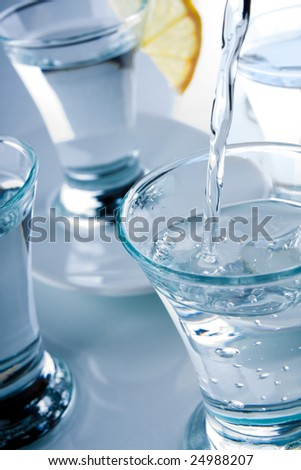 Several short glasses and lemon on the glass table - stock photo