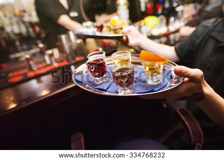 Several shot glasses on silver tray in bar setting - stock photo