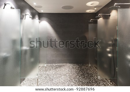several showers seperated with walls of glass and wall and floor with dark tiles - stock photo