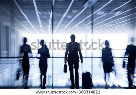Several silhouettes of businesspeople interacting  background airport - stock photo