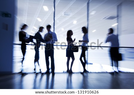 Several  silhouettes of businesspeople interacting  background business center - stock photo