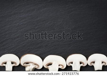 Several sliced mushrooms isolated on dark grey slate stone copyspace. - stock photo